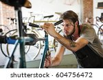 a man working in a bicycle... | Shutterstock . vector #604756472