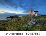 Rocky coastline with lighthouse. - stock photo