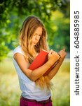 pretty severe young girl reads... | Shutterstock . vector #604885985