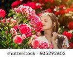 Stock photo beautiful girl standing in the park of roses a young girl smelling the blooming roses 605292602