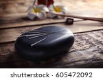 Small photo of Acupuncture needles with stone on wooden background