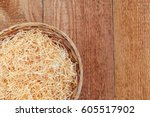 Small photo of Wicker basket with wood wool curls on wooden uncouth Board, rustic background, top view, copy space, gift packaging background