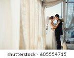 groom holds bride's waist... | Shutterstock . vector #605554715