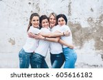 Small photo of Group of four young diverse girls wearing blank white tshirt and jeans posing against rough street wall, fashion urban clothing style, mockup for t-shirt print store