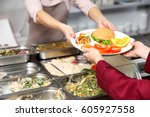 Stock photo pleasant woman giving lunch to school girl in cafeteria 605927558