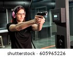 a woman firing a hand gun at an ...