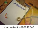 Small photo of Clipboard with a white paper on which is written the AMOEBIASIS, pen, stethoscope, glasses and medicine on a wooden table, the concept of health - vintage