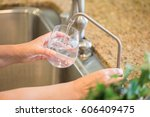 Small photo of Woman Pouring Fresh Reverse Osmosis Purified Water Into Glass in Kitchen.
