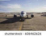 Small photo of Aircraft tugging to a boarding sleeve by a pusher tug