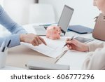 Small photo of Financial advisor and woman meeting in the office, the customer is reading and signing a contract