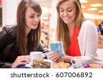 two women looking at mobile... | Shutterstock . vector #607006892