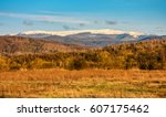 high mountain ridge snowy peaks over the hillside with forest - stock photo