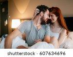 happy couple in bed showing... | Shutterstock . vector #607634696