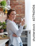 home. young woman in kitchen | Shutterstock . vector #607960406
