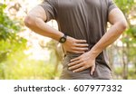 sport injury  man with back pain | Shutterstock . vector #607977332