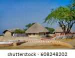 Small photo of KUTCH, GUJARAT, INDIA - DECEMBER 27, 2016: A group of Bhungas at Hodka village, Kutch. Gujarat, India. 'Bhunga' is a traditional Kutchi Mud Hut. Thatched roof, Decorative hand painted motifs.