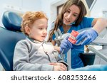female dentist showing the... | Shutterstock . vector #608253266