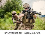 Small photo of Two military man snipers with airsoft automatic rifle with a telescopic sight lies in grass in forest. Focus on rifle of first man