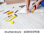 repairman laying laminate... | Shutterstock . vector #608403908
