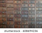 Small photo of primitive wooden apothecary or catalog cabinet with partially open drawers - storage and sorting concept or just retro background
