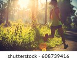 Small photo of Young fitness woman running at morning tropical forest trail