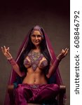 Small photo of Eastern beautiful brunette woman in afghani pants, purdah and adornment.