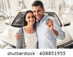 Stock photo visiting car dealership beautiful couple is holding a key of their new car looking at camera and 608851955