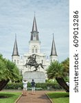 Small photo of Two men admiring statue of Andrew Jackson in Jackson Square Park, New Orleans with St. Louis Cathedral behind