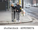 young woman assisting blind man ... | Shutterstock . vector #609058076
