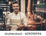 handsome bartender in apron is... | Shutterstock . vector #609098996