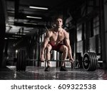 Small photo of young shirtless athlete doing deadlift exercise in the gym.