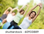 Group of people in a pilates class outdoors - stock photo