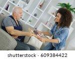 carer passing meal to elderly... | Shutterstock . vector #609384422