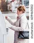 woman drawing out money from atm | Shutterstock . vector #609465002
