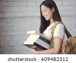 asian students holding books at ... | Shutterstock . vector #609482312