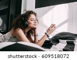 Small photo of Woman in large headphones listens to the music sitting on bed