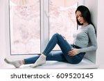 Small photo of Pretty brunette sits on white windowsill
