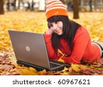 Young woman in autumn orange leaves with laptop. Fall sale. Outdoor. - stock photo