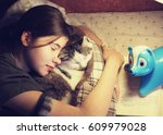 Stock photo teenage girl hug cuddle cat in bed with book and lamp 609979028
