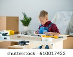 pensive little boy standing at... | Shutterstock . vector #610017422
