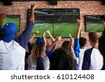 Stock photo rear view of friends watching game in sports bar celebrating 610124408