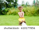 Stock photo boy with funny face expression and tongue playing with dog 610177856