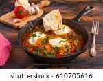 Small photo of Shakshouka or shakshuka, poached eggs in a sauce of tomatoes, beans, onion and spices, in a black cast iron skillet on the wooden table.