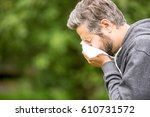 Small photo of Man with allergy or an infection sneezing