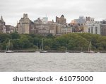 Sailboats along a marina in uptown Manhattan with many buildings in the background. - stock photo