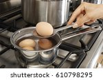woman boiling eggs | Shutterstock . vector #610798295
