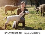 Stock photo woman is feeding a lamb with bottle of milk concept animal welfare and rearing 611028098