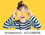 Stock photo girl with oranges on the background in the studio 611168096