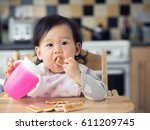 asian baby girl eating toasted... | Shutterstock . vector #611209745
