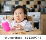 asian baby girl eating toasted... | Shutterstock . vector #611209748